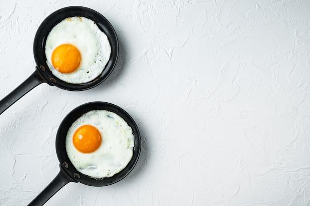 Uova fritte con pomodorini e pane per colazione in padella in ghisa, sul tavolo bianco, vista dall'alto laici piatta