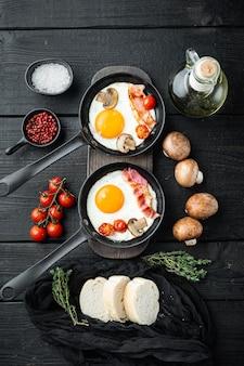 Uova fritte con pomodorini e colazione a base di pane in padella in ghisa, su tavolo di legno nero