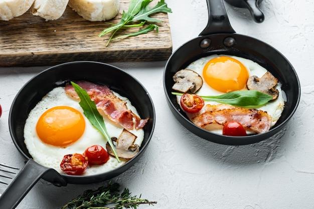 Uova fritte con pomodorini e pane per colazione in padella in ghisa, sul tavolo bianco