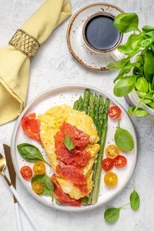 Uova fritte con asparagi verdi e salmone, pomodorini e spinaci freschi.
