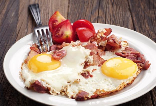 Uova fritte con prosciutto e pomodoro su tavola di legno