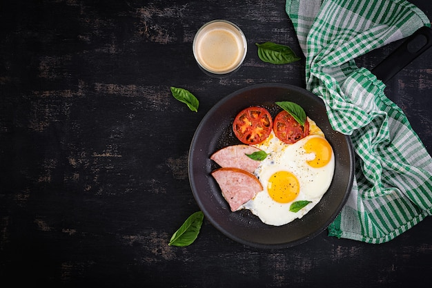 Uova fritte con prosciutto e pomodori. deliziosa colazione inglese. brunch. keto, dieta paleo. vista dall'alto, dall'alto
