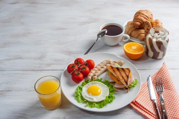 Uova fritte con salsicce e verdure sul piatto