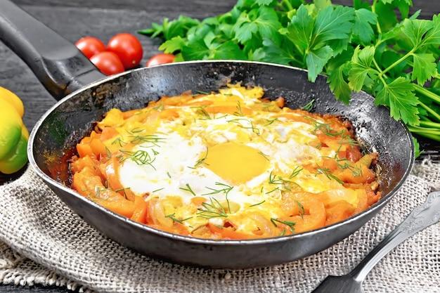 Uova fritte con pomodori, peperoni dolci, cipolle ed erbe aromatiche in una padella su tela, prezzemolo, forchetta su fondo di legno