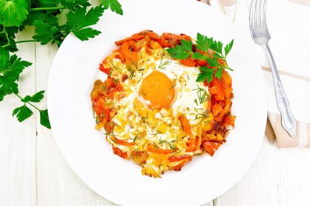 Uova fritte con pomodori, peperoni, cipolle ed erbe aromatiche in un piatto, tovagliolo, prezzemolo e forchetta su tavola di legno dall'alto