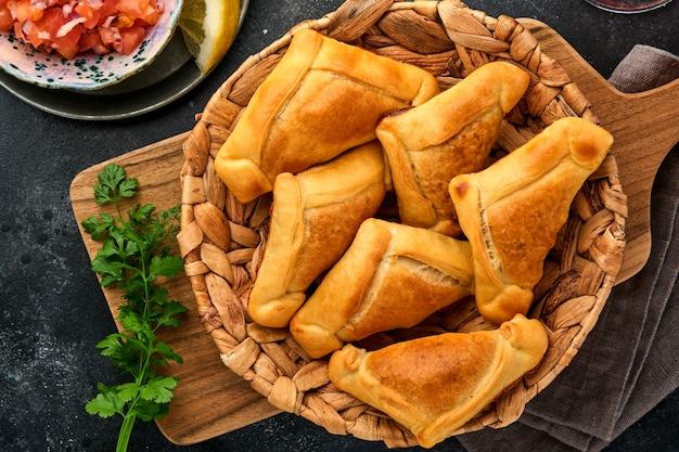 Empanadas fritte con salsa di coriandolo, carne, uova, pomodoro e peperoncino su sfondo nero. piatto tipico cileno. concetto di festa dell'indipendenza dell'america latina e del cile.