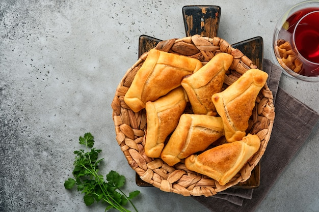 Empanadas fritte con salsa di coriandolo, carne, uova, pomodoro e peperoncino su sfondo grigio. piatto tipico cileno. concetto di festa dell'indipendenza dell'america latina e del cile.