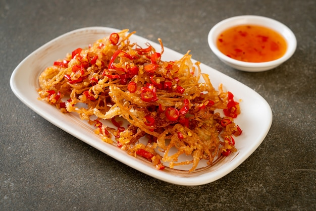 Funghi enoki fritti o funghi aghi d'oro con sale e peperoncino - stile alimentare vegano e vegetariano