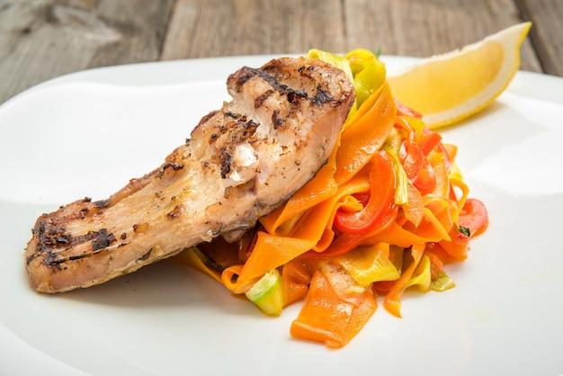 Insalata fritta della carpa e della verdura fresca del pesce su superficie di legno