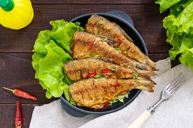 Carpa di pesce fritto (sazan) su una padella in ghisa con foglie di lattuga su un tavolo di legno scuro. vista dall'alto.