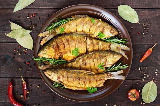 Carpa di pesce fritto (sazan) su una ciotola di ceramica con rami di rosmarino su un tavolo di legno scuro. vista dall'alto.