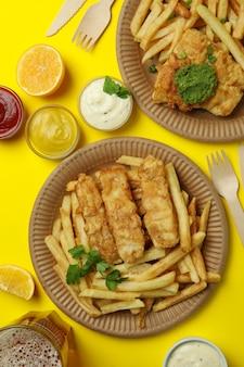 Pesce fritto e patatine fritte isolato su giallo