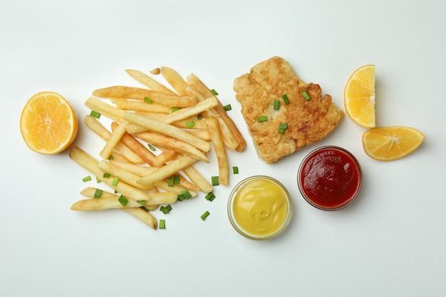 Pesce fritto e patatine fritte, salse e limone su bianco