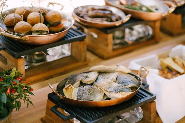 Pesce fritto su una padella di rame su un fornello sullo sfondo di mini hamburger in cucina
