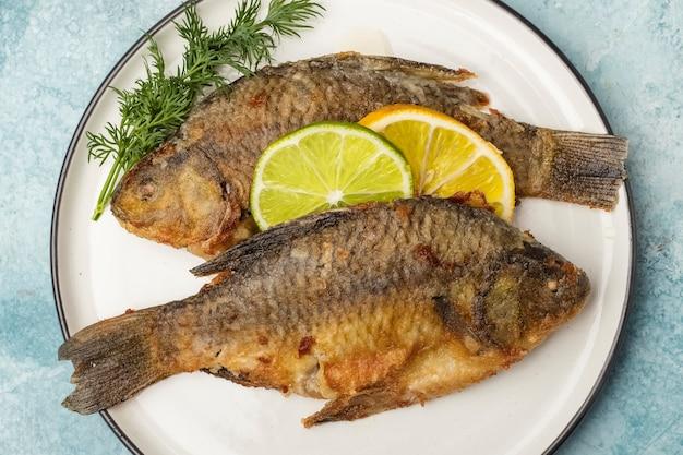 Crucian di pesce fritto su un piatto con fette di limone e lime, vista dall'alto. pasto pronto. sfondo blu