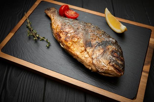 Pesce fritto, longarone o dorada, su tavola, su fondo nero