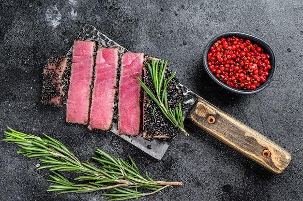 Fette di bistecca di tonno di pesce fritto su una mannaia di carne