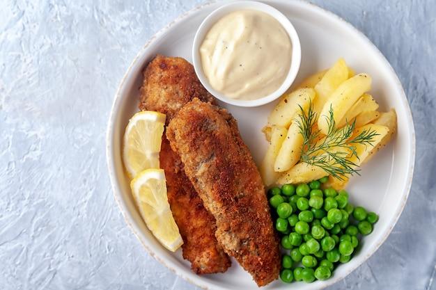 Fritto di pesce con patate fritte, piselli e limone