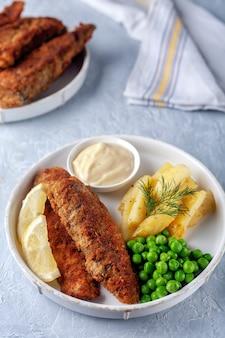 Pesce fritto con patate fritte piselli e limone