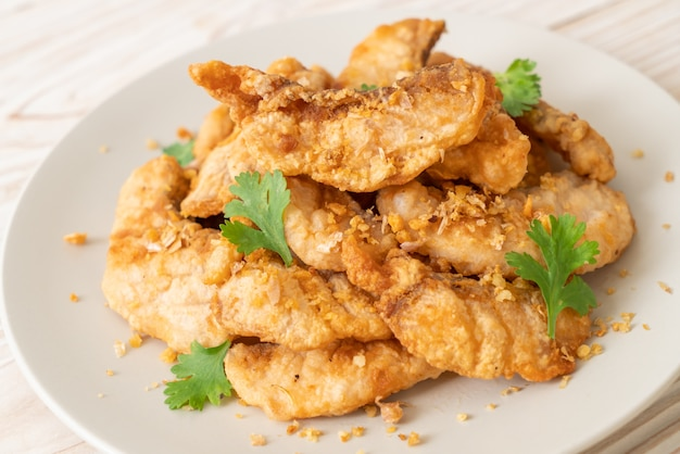 Pesce fritto con aglio su un piatto