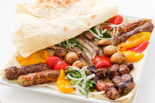 Piatto di cibo fritto. menu del ristorante. carne e verdure disposte su focaccia di grano.