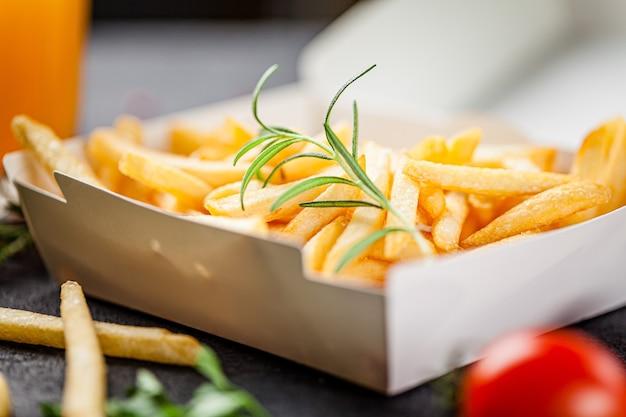 Patatine fritte in una scatola bianca di carta ecologica
