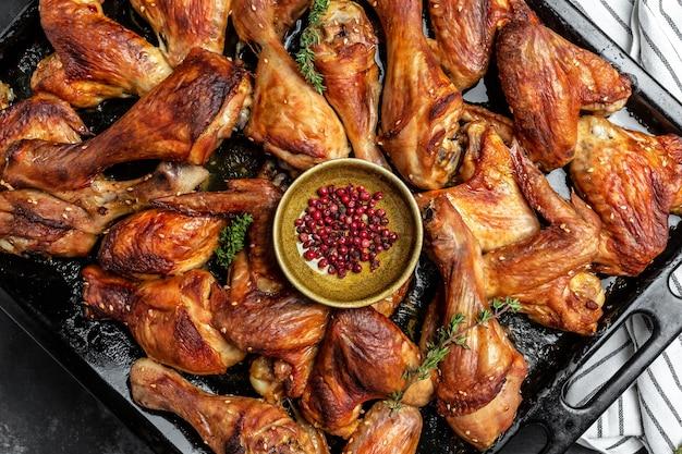 Alette e cosce di pollo dorate fritte sulla teglia