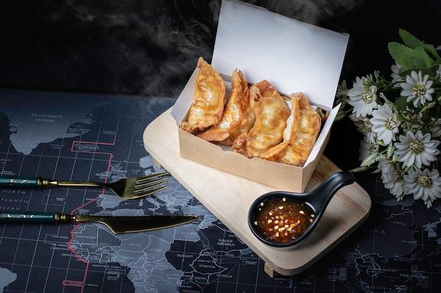 Gyoza fritto, patatine fritte calde in una scatola di cartone affumicata, sfondo nero.