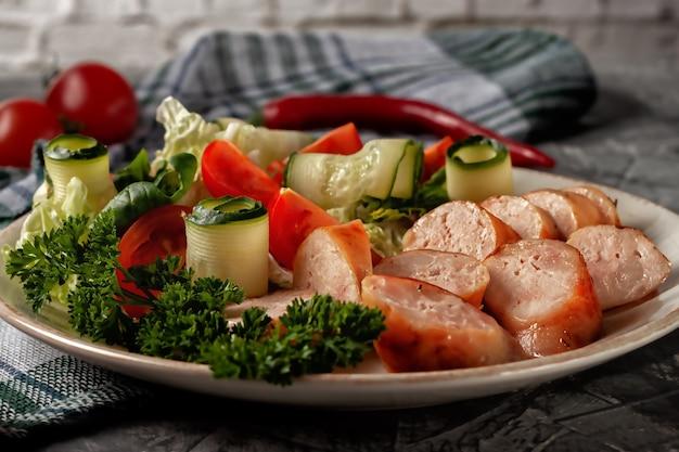 Salsiccia fatta in casa fritta con verdure fresche su un piatto