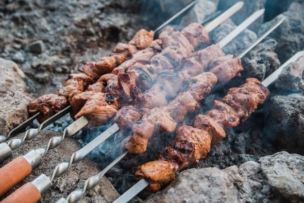 Il succoso shish kebab fritto su spiedini è cotto sul fuoco