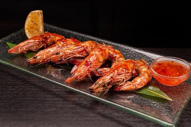 Gamberoni fritti su foglia di bambù, su piatto trasparente, con limone e salsa