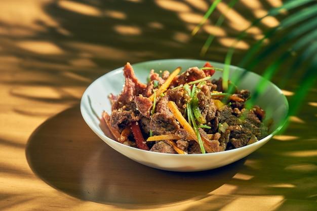 Agnello fritto con cumino e verdure in un piatto bianco. cucina cinese.