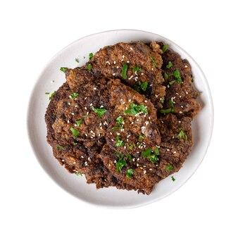 Pezzi di fegato fritto su un piatto isolato su uno sfondo bianco. vista dall'alto.