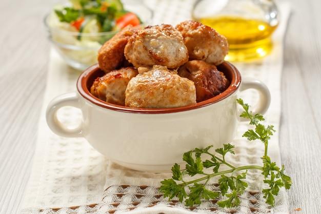 Cotolette di carne fritte in una ciotola di zuppa di ceramica, bottiglia con olio di semi di girasole e insalata di cetrioli e pomodori freschi in una ciotola di vetro su carta da cucina bianca.