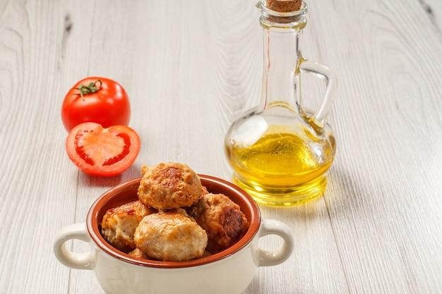 Cotolette di carne fritte in ciotola di zuppa di ceramica, pomodori rossi e bottiglia di vetro con olio di girasole su tavole di legno grigie.