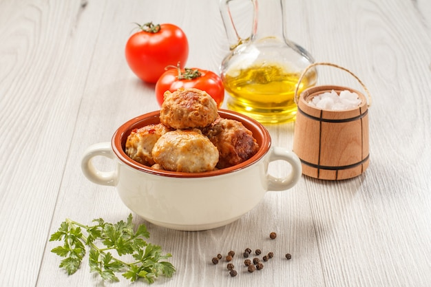 Cotolette di carne fritte in ciotola di zuppa di ceramica, pomodori rossi, bottiglia di vetro con olio di semi di girasole, cantina a botte di sale in legno e ramo di prezzemolo fresco su tavole di legno grigie.