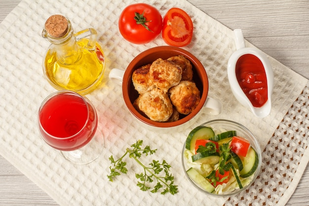 Cotolette di carne fritte in ciotola di zuppa di ceramica, pomodori rossi, salsiera in ceramica bianca con salsa di pomodoro, bicchiere di vino rosso, asciugatutto e bottiglia di vetro con olio di girasole su tavole di legno grigie. vista dall'alto