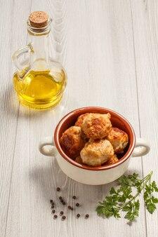 Cotolette di carne fritte in ciotola di zuppa di ceramica bianca, bottiglia di vetro con olio di semi di girasole, ramo di prezzemolo fresco e pepe nero su tavole di legno grigie.