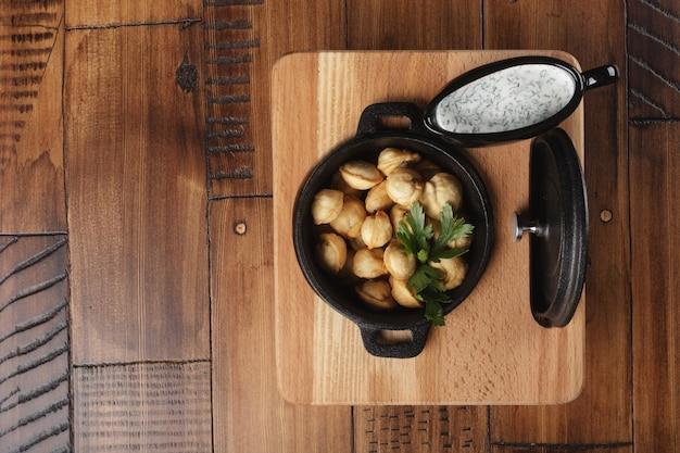 Gnocchi di carne fritti pelmeni, chuchpara in padella nera. fondo in legno.