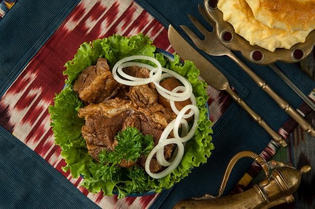 Fritto di carne e anelli di cipolla su una tovaglia orientale