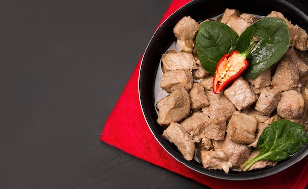Carne fritta in padella su sfondo nero.