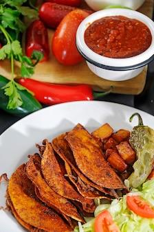 Tacos di carne fritti con insalata patatine fritte e peperoncino toreado