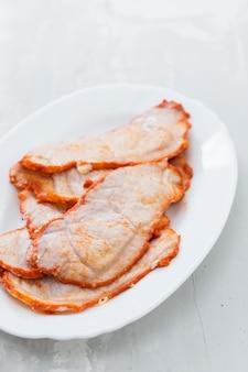 Carne fritta sul piatto bianco su fondo in ceramica