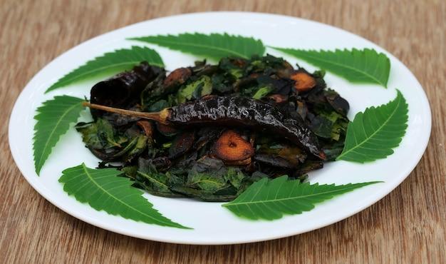 Foglie di neem fritte con su un piatto bianco