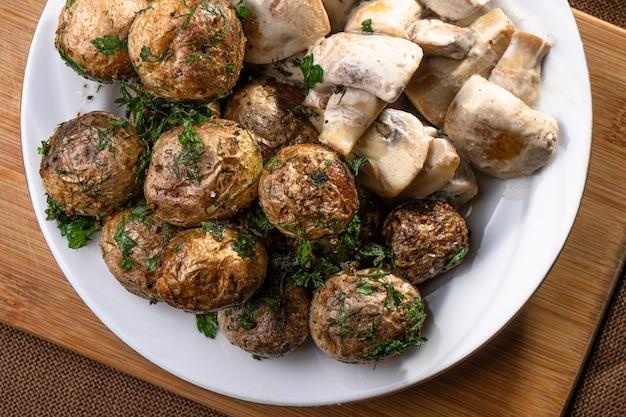 Patate novelle fritte in crosta con funghi prataioli in salsa cremosa close-up su una tavola di legno. stuzzicanti piatti fatti in casa o al ristorante