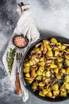 Funghi di ostrica fritti con le patate in una pentola. vista dall'alto. spazio per il testo