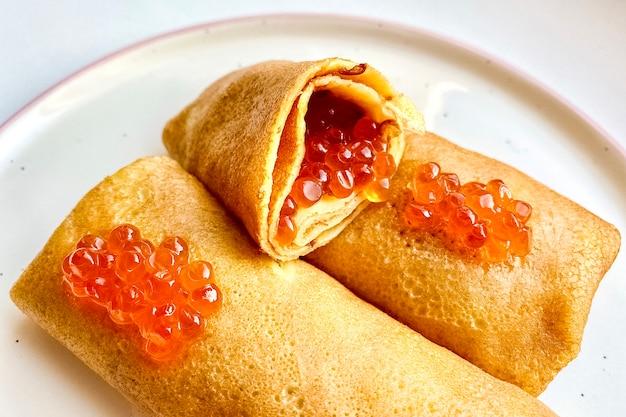 Frittelle fritte con caviale di salmone rosso su un piatto. avvicinamento