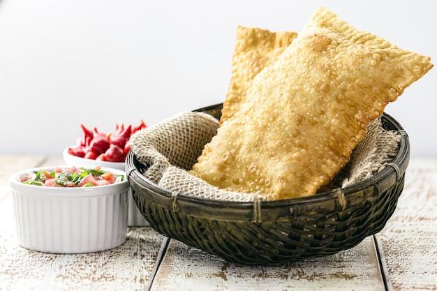 Pasta fritta con patate, salsa piccante servita calda.