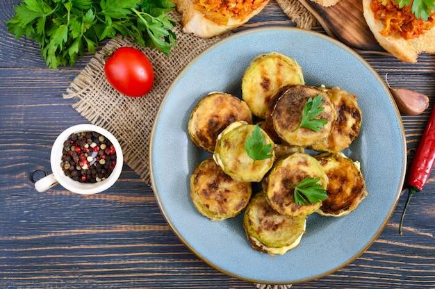 Pezzi fritti di zucchine con maionese su un piatto di ceramica su un tavolo di legno. vista dall'alto.