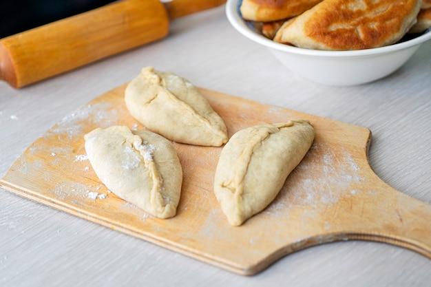 Le torte non fritte si trovano sul bordo di legno. cucina casalinga. cuocere a casa.